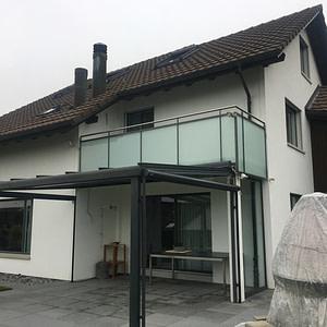 Neue Balkonverglasung aus Flachstahl-Pfosten, Profilstahlrohr, CNS-Handlauf und Mattglasfüllung